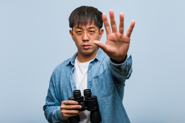 Young chinese man holding a binoculars putting hand in front