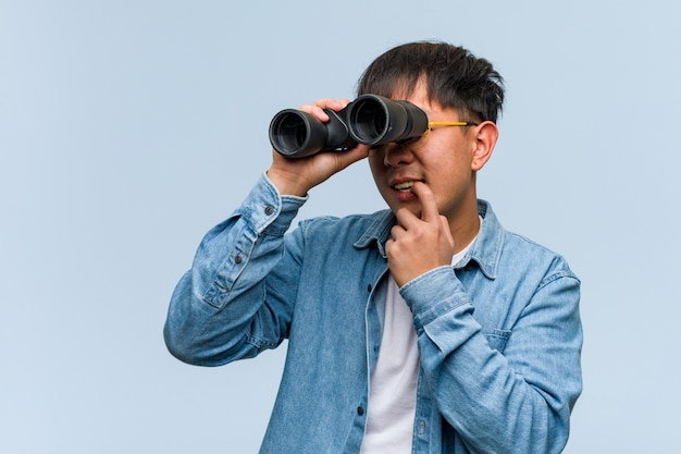 Young chinese man holding a binoculars relaxed thinking about something looking a copyspace