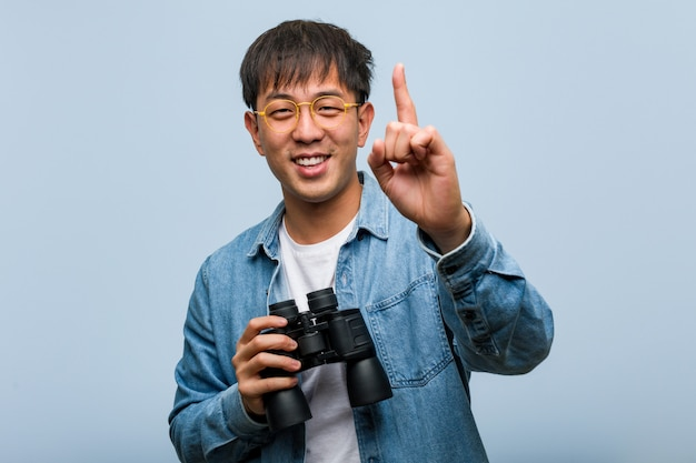 Young chinese man holding a binoculars showing number one