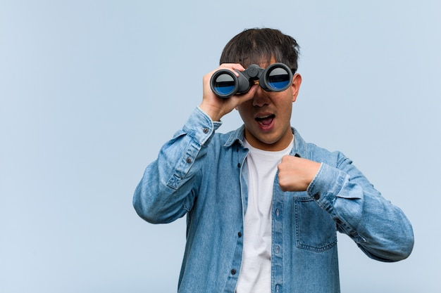 Young chinese man holding a binoculars surprised, feels successful and prosperous