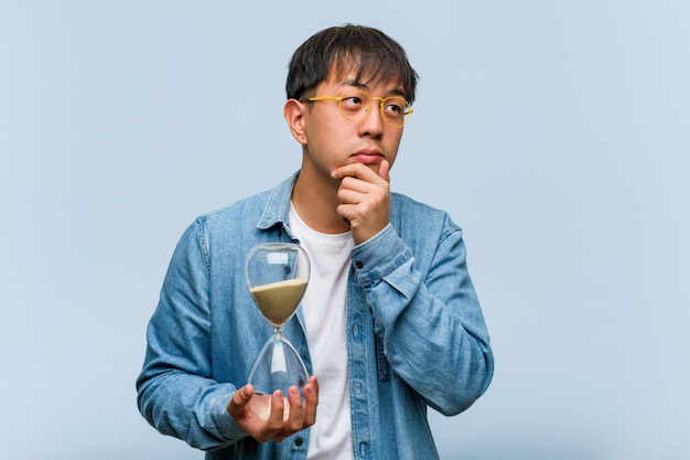 Young chinese man holding a sand timer doubting and confused