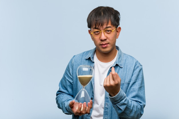 Young chinese man holding a sand timer inviting to come