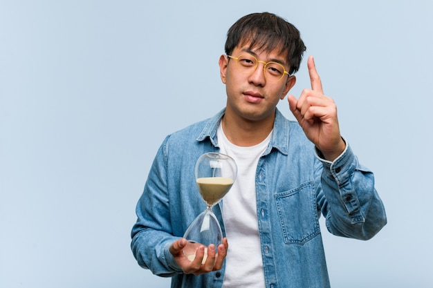 Young chinese man holding a sand timer showing number one