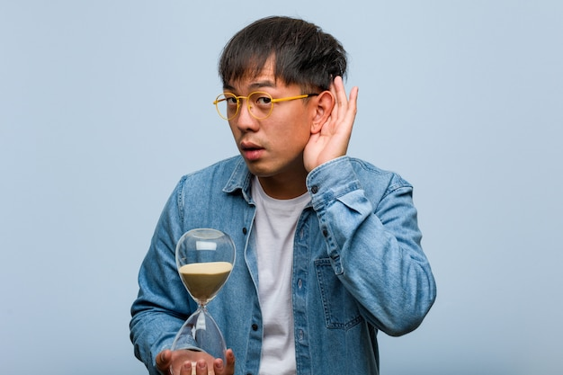 Young chinese man holding a sand timer try to listening a gossip