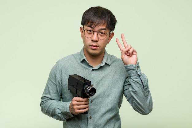 Young chinese man holding a vintage camera showing number two