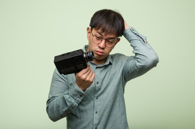 Young chinese man holding a vintage camera worried and overwhelmed