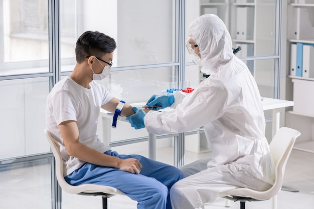 Молодой китаец в маске сидит в лаборатории, пока врач в защитном комбинезоне берет его кровь в шприц для анализа