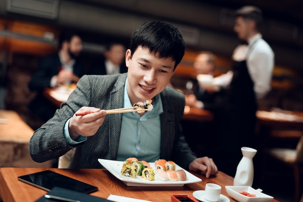 Young chinese man is eating sushi