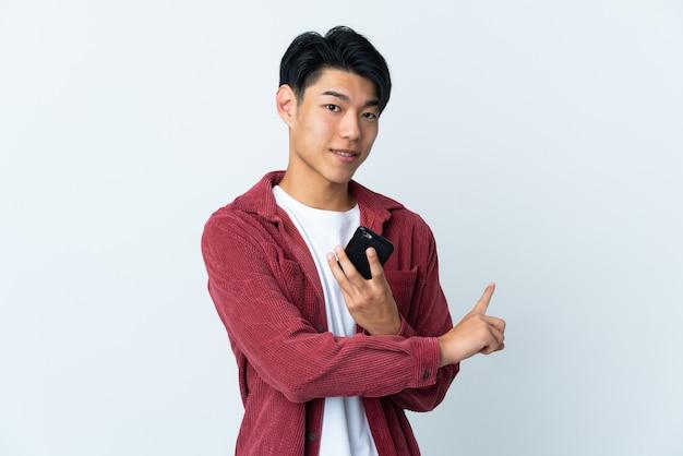 Молодой китаец изолирован на белой стене, используя мобильный телефон и указывая назад