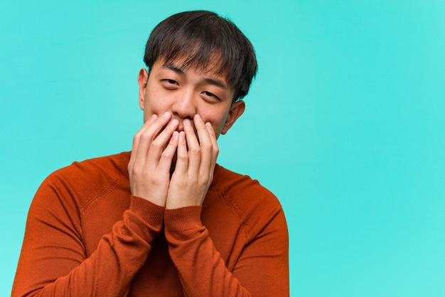 Young chinese man laughing about something, covering mouth with hands