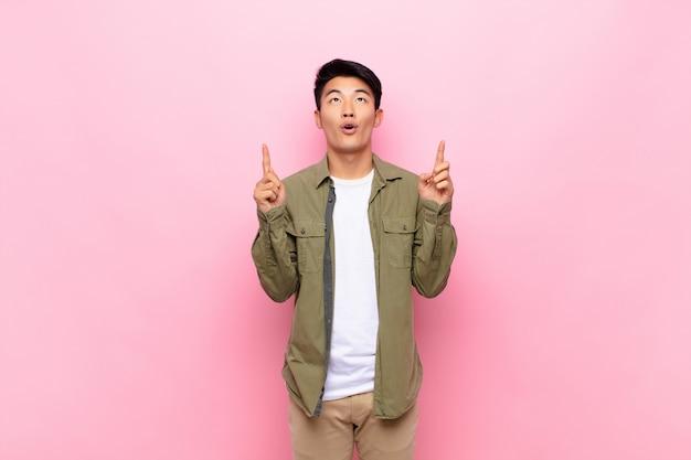 ショックを受けた、驚いて、口を開けて探している若い中国人男性、両手で上向きにフラットカラーの壁にスペースをコピーする
