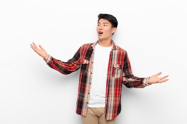 Молодой китаец исполняет оперу или поет на концерте или шоу, чувствуя себя романтичным, артистичным и страстным на плоской цветной стене