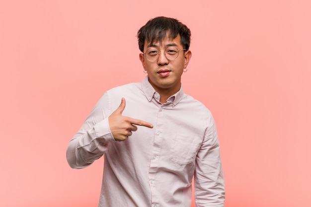 Young chinese man person pointing by hand to a shirt copy space, proud and confident