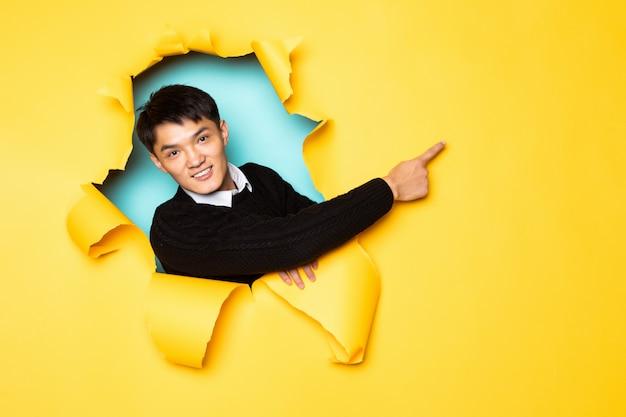 Сторона молодого китайского человека остроконечная с руками держит голову в отверстии сорванной желтой стены. мужская голова в разорванной бумаге.
