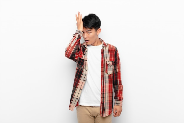 Молодой китаец поднимает ладонь ко лбу, думая, что ой, совершив глупую ошибку или вспомнив, чувствуя себя тупым на фоне плоской цветной стены