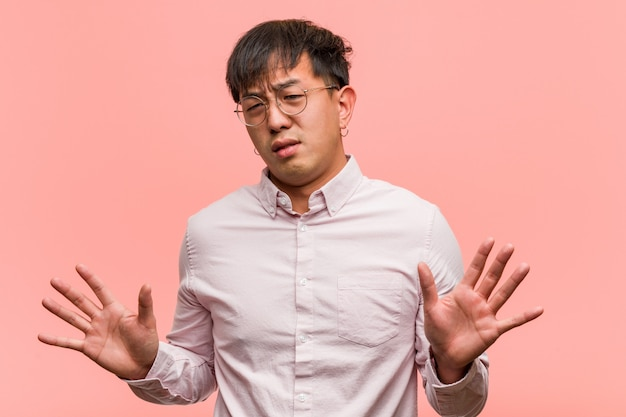 Young chinese man rejecting something doing a gesture of disgust