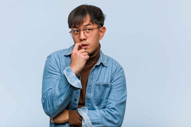 Young chinese man relaxed thinking about something looking at a copy space