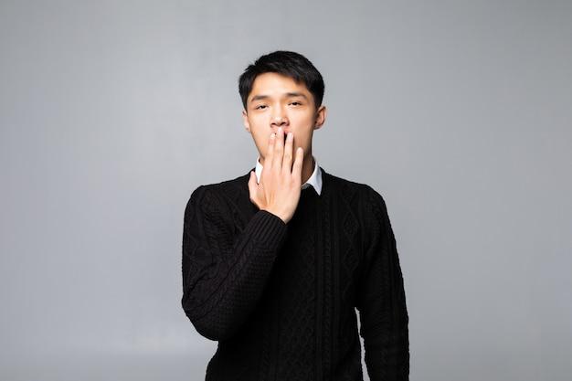 젊은 중국 남자는 격리 된 흰 벽 위에 서 실수로 손으로 입 취재 충격. 비밀 개념.