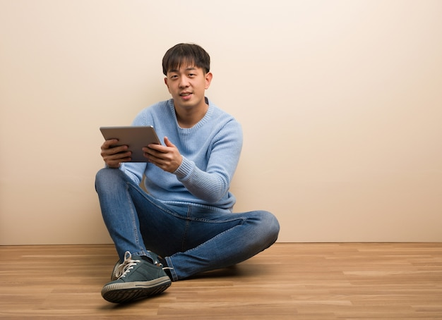 Young chinese man sitting using his tablet cheerful with a big smile