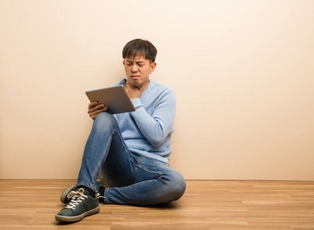 Young chinese man sitting using his tablet coughing, sick due a virus or infection