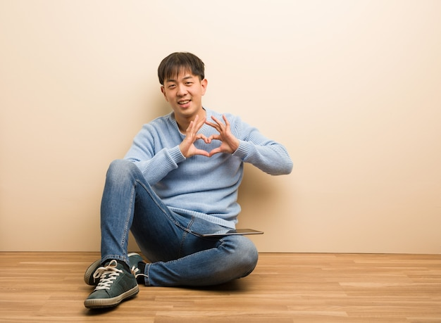 Young chinese man sitting using his tablet doing a heart shape with hands
