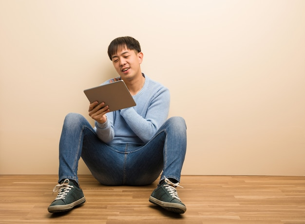 Young chinese man sitting using his tablet doing a romantic gesture