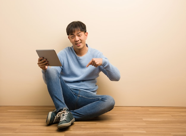 Young chinese man sitting using his tablet pointing to the bottom with fingers