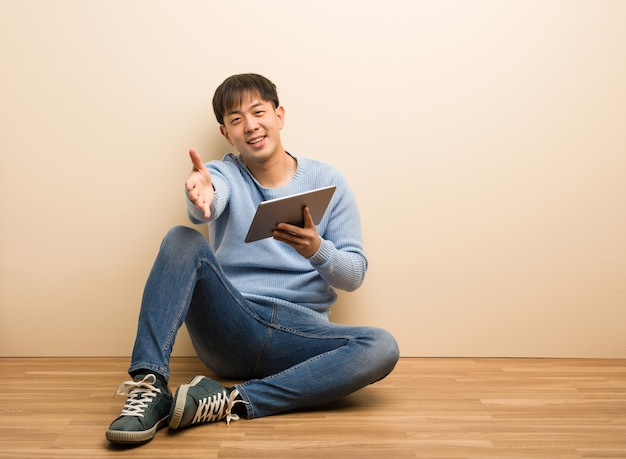 Young chinese man sitting using his tablet reaching out to greet someone