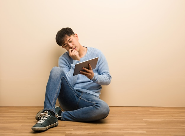 Young chinese man sitting using his tablet relaxed thinking about something looking at a copy space