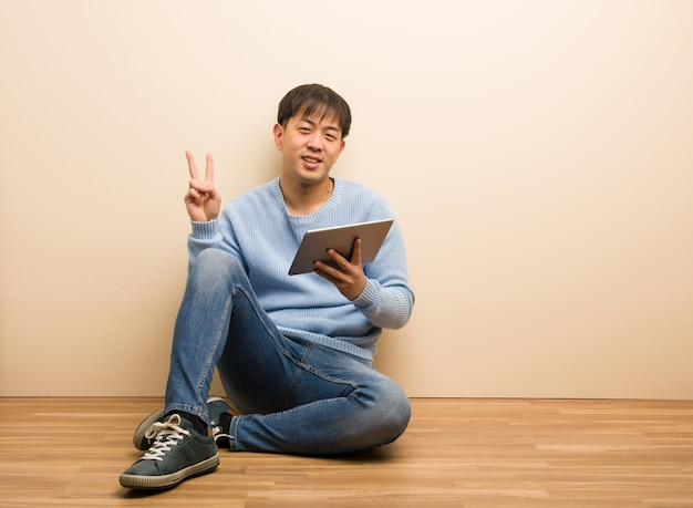 Young chinese man sitting using his tablet showing number two