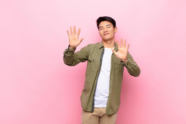 Молодой китаец улыбается и выглядит дружелюбно, показывает десятый или десятый номер рукой вперед, считая на плоской цветной стене