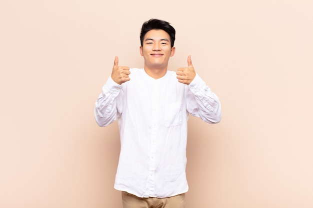 Young chinese man smiling broadly looking happy, positive, confident and successful, with both thumbs up on flat color wall