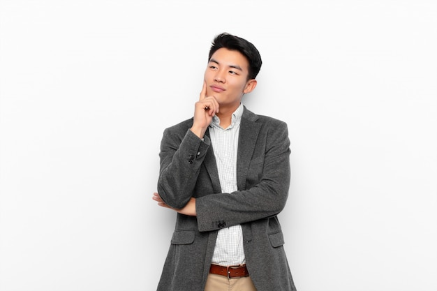 Young chinese man smiling happily and daydreaming or doubting, looking to the side on flat color wall