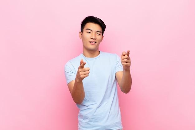 陽気で成功した、幸せな態度を指して、フラットカラーの壁に手で銃のサインを作って笑顔の若い中国人男性