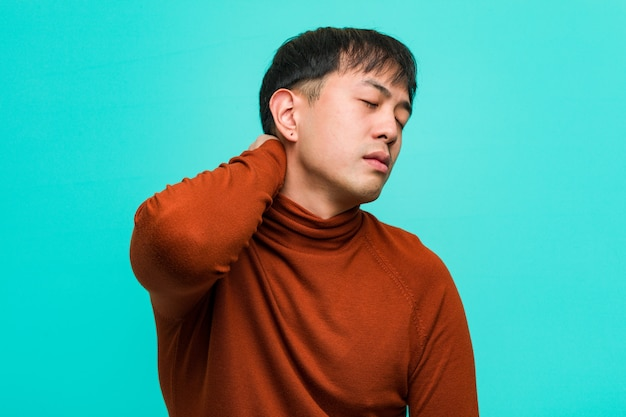 Young chinese man suffering neck pain
