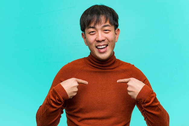 Young chinese man surprised, feels successful and prosperous