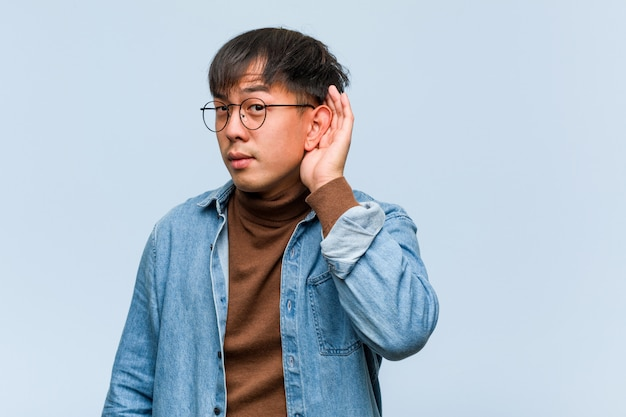Young chinese man try to listening a gossip