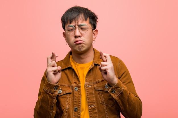 행운을 위해 손가락을 건너 재킷을 입고 젊은 중국 남자