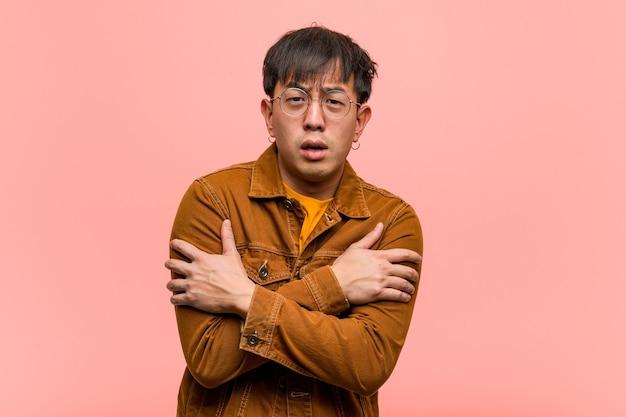 Молодой китаец в куртке замерзает из-за низкой температуры