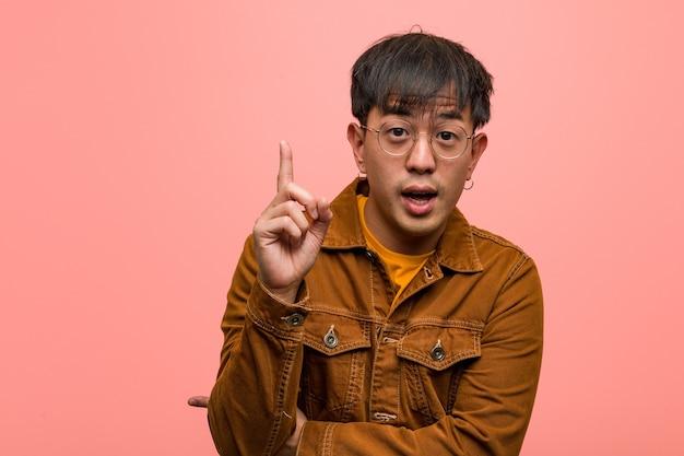 素晴らしいアイデア、創造性の概念を持つジャケットを着ている若い中国人男性