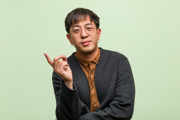 Young chinese man wearing a cool clothes style against a green