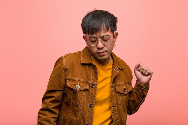 Young chinese man wearing a jacket dancing and having fun