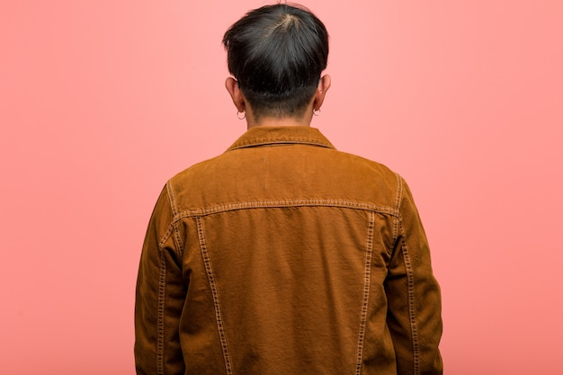 Young chinese man wearing a jacket from behind, looking back