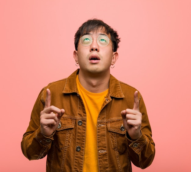 Young chinese man wearing a jacket surprised pointing up to show something