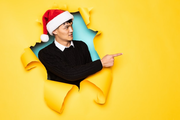 Young chinese man with santa hat pointed side with hands keeps head in hole of torn yellow wall. male head in ripped paper.