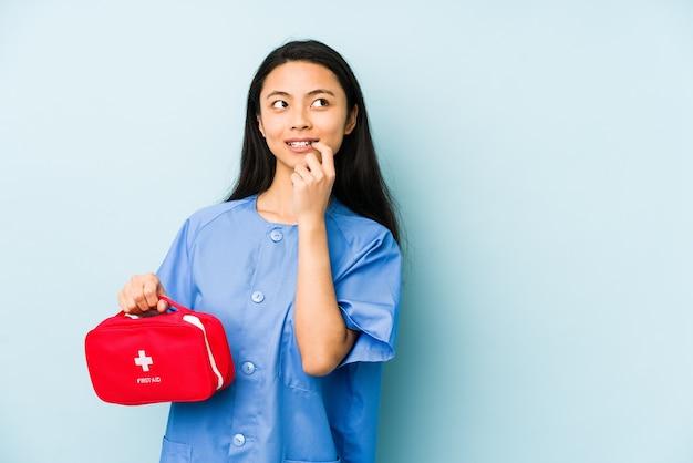 Молодая китайская медсестра, изолированная на синем фоне, чувствует гордость и уверенность в себе, пример для подражания.