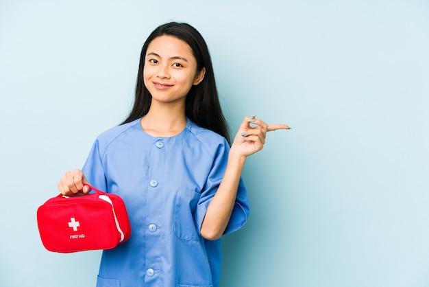 Молодая китайская медсестра изолирована на синей стене, касаясь затылка, думая и делая выбор.