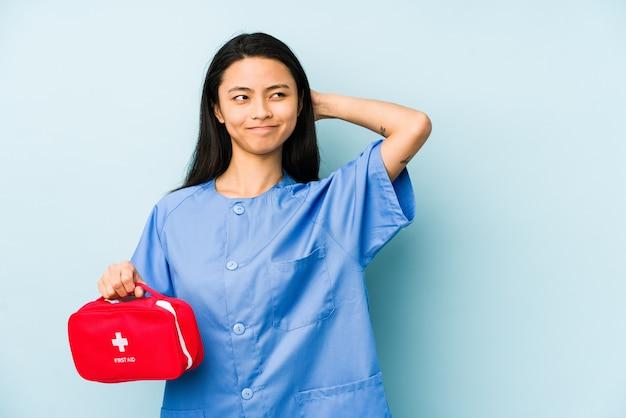 Молодая китайская медсестра, изолированная на синей стене, пытается слушать сплетню.