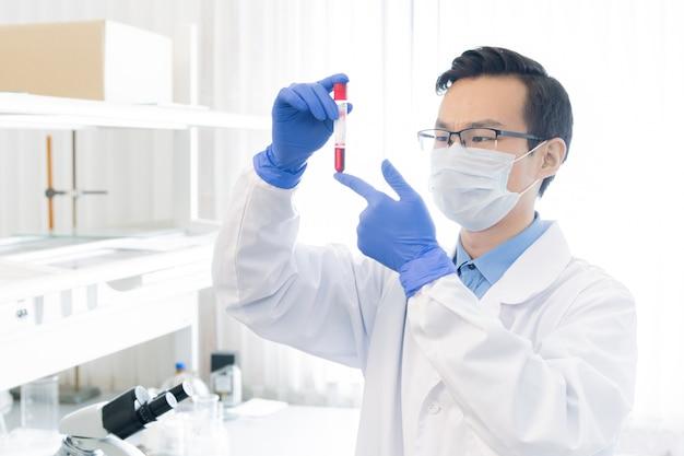 실험실에서 그 특성을 연구하는 동안 붉은 액체 물질로 플라스크를보고 보호 작업복에 젊은 중국 연구원