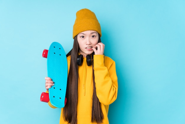 Young chinese skater woman isolated biting fingernails, nervous and very anxious.